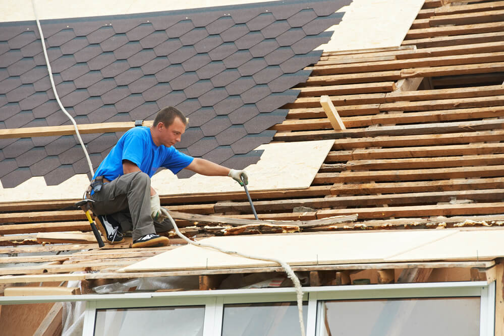 This is a picture of a roofing contractor working on a roof in Naples.